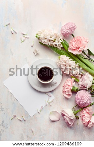 Overhead view of morning cup of coffee, empty card and bouquet of flowers on pastel concrete background with copy space #1209486109