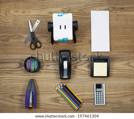 Overhead view of office materials placed on rustic wood.  Items include stapler, scissors, ruler, address book, envelopes, paper clips, tape dispenser, note pad, pencils, and calculator.