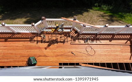 Overhead view of outdoor wooden deck being remodeled with power and hand tools on floor boards Photo stock ©