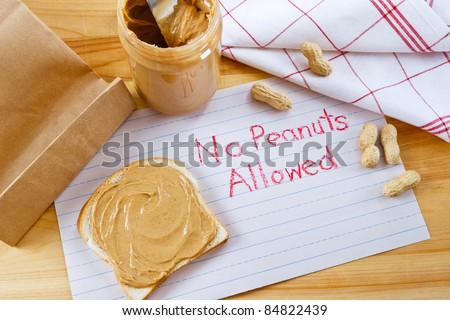 Overhead view of peanut butter on bread with red crayon warning against peanuts which are a dangerous allergen for many children and adults.