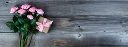 Overhead view of pink roses and giftbox on rustic wood for Mothers Day concept