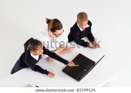 overhead view of primary teacher and students using laptop