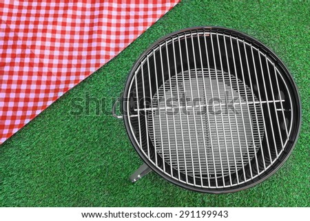 Overhead View Of Red Picnic Tablecloth And Empty BBQ Grill Appliance On The Summer Green Lawn Background