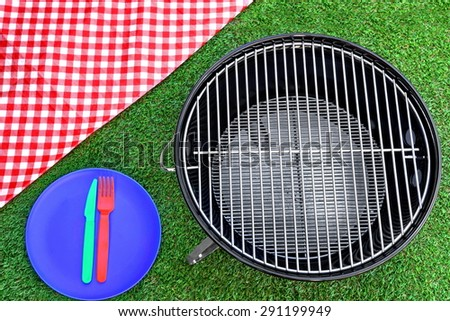 Overhead View Of Red Picnic Tablecloth, Plate, Fork, Knife, BBQ Grill  On The Summer Green Lawn Background