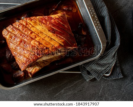 Overhead view of roasted pork belly with crust on a baking tray Stockfoto ©