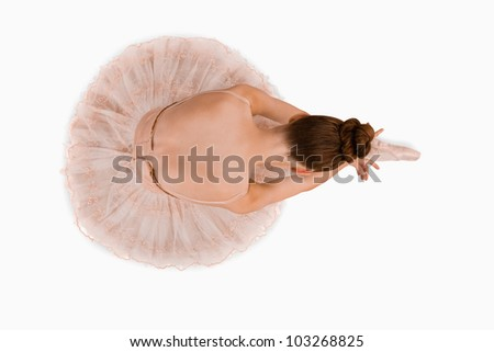 Overhead view of sitting ballerina against a white background