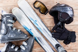 Overhead view of ski accessories placed on rustic wooden table. Items included helmet, goggles, ski, gloves and ski boots. Winter sport leisure time concept.