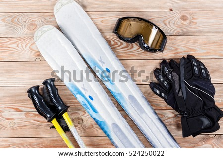 Overhead view of ski accessories placed on rustic wooden table. Items included ski, goggles, gloves and ski sticks. Winter sport leisure time concept. #524250022