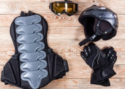 Overhead view of ski and snowboard accessories placed on rustic wooden table. Items included helmet, goggles, gloves and back protection. Winter sport leisure time concept.