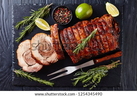 overhead view of sliced roast pork roulade -  Porchetta, delicious pork roast of Italian culinary holiday tradition on a slate tray with rosemary and lime, close-up, flatlay