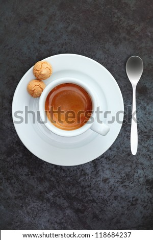 Overhead view of strong frothy espresso coffee in a cup and saucer with two traditional macaroons and a silver teaspoon