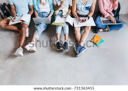 Overhead view of student's legs in trendy colorful shoes. Boys and girls with laptops and textbooks doing their homework together.