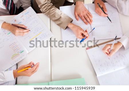 overhead view of teacher tutoring students in classroom