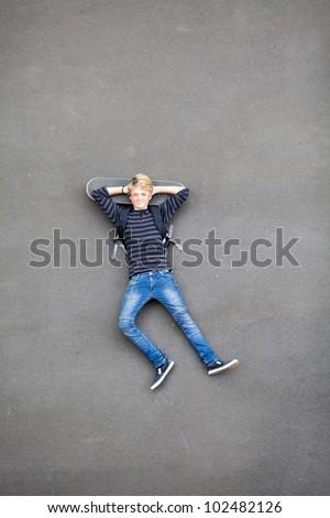 overhead view of teen skateboarder lying on his skateboard