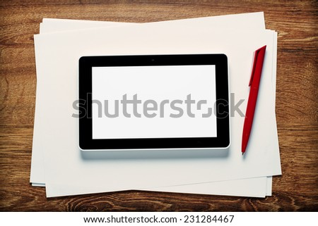 Overhead view of the blank white screen of a tablet and pen on blank paper ready for a meeting or taking notes in a communication concept, with copyspace
