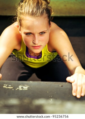 Overhead view of the determined expression on the face of a young woman traceur participating in parkour.