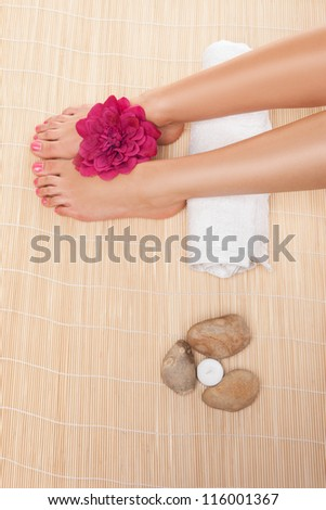 Overhead view of the feet of a woman resting on a rolled white towel with a flower and hot stones while having a spa treatment