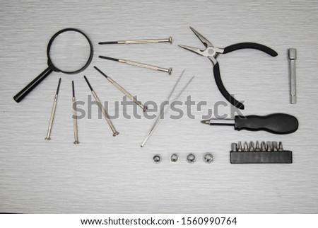 Overhead view of tools for watch repair, computer repair, jewelry repair and smartphone repair