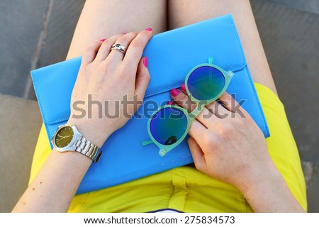 Overhead view of trendy girl accessories blue handbag and green sunglasses . Summer outfit