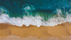 Overhead view of waves hitting the yellow sand and blue ocean