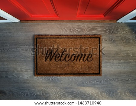 Overhead view of welcome mat outside inviting front door of house