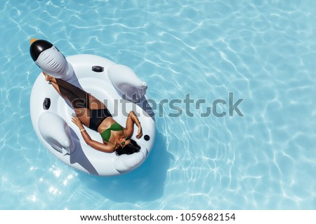 Overhead view of woman in bikini resting on an inflatable swan in swimming pool. Female sunbathing on inflatable toy floating in pool.