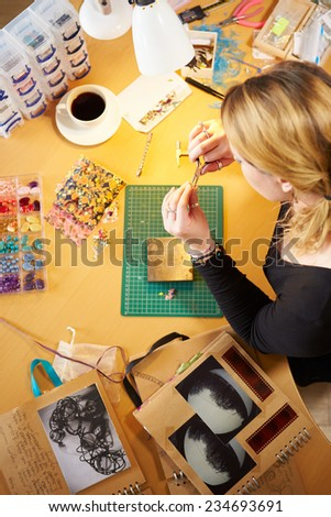 Overhead View Of Woman Making Jewelry At Home