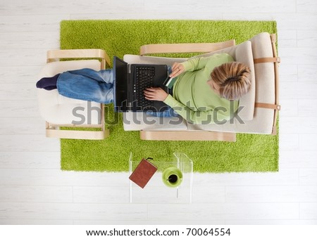 Overhead view of woman sitting in armchair shopping from home with computer and credit card.?