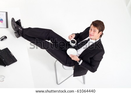 overhead view of young businessman drinking coffee in office