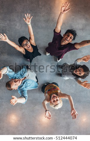 Overhead view of young people standing together looking up at camera with their arms raised. University students cheering.