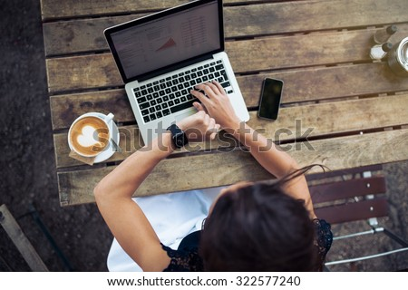 Overhead view of young woman checking time on her smartwatch while working on her laptop at a cafe. Top view shot of female sitting at a table with a cup of coffee, laptop and mobile phone.