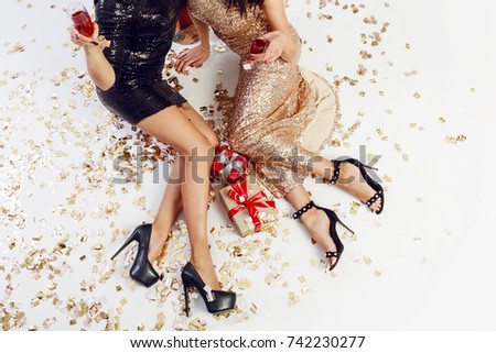 Overhead view on sexy women legs on heels , golden confetti, sparkly  evening  dress. Two   elegant girls celebrating new year , drinking wine.  Christmas gift boxes.