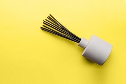 Overhead view to aroma reed diffuser on yellow background, trend and mod colors of 2021 year Ultimate Gray and Illuminating