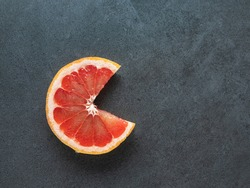 overhead view to isolated cut pink grapefruit has open mouth like in popular computer game with copy space on dark background