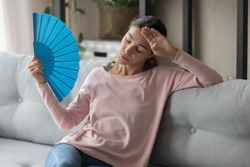 Overheated female sitting on couch in living room at hot summer weather day feeling discomfort suffers from heat waving blue fan to cool herself, girl sweating dwelling without air conditioner concept