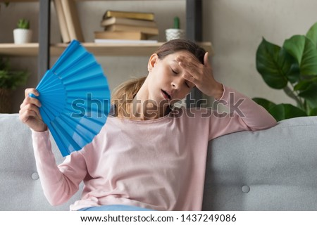 Overheated millennial woman sit on couch at home feel warm waving with hand fan cooling down, sweating girl relax on sofa in living room hold waver suffer from heat, no air conditioner system