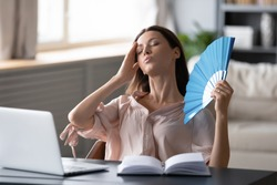 Overheated woman waving fan, sitting at desk with laptop at home, stressed young female suffering from heating at home, feeling discomfort, hot summer weather or fever, heatstroke concept