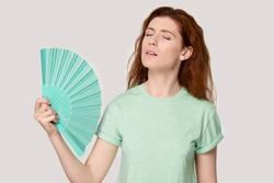 Overheated young red-haired woman using fan, cooling herself, suffering from hot summer weather or high temperature inside, heat stroke, feeling unwell, sweating, isolated on grey studio background.