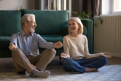 Overjoyed active elderly husband and wife sit on floor with mudra hands practice yoga at home, smiling senior 60s couple meditate relieve negative emotions, healthy lifestyle, stress free concept