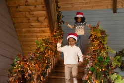 Overjoyed African American children running downstairs to open gifts on Christmas morning, laughing little girl and boy wearing festive red cap and warm sweater celebrating New Year, winter holidays