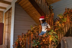 Overjoyed African American little girl running downstairs on Christmas morning to open gifts, excited child wearing festive red cap and warm sweater celebrating New Year, winter holidays