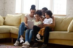 Overjoyed african American young family with little kids sit relax on couch at home watching funny video on tablet, happy biracial parents enjoy weekend with small children using modern pad device