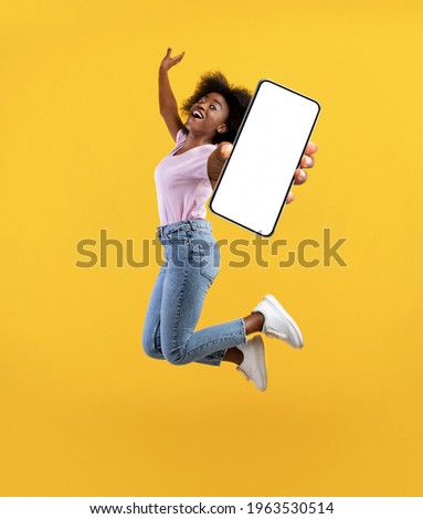 Overjoyed african american young lady showing empty smartphone screen while jumping up over yellow studio background, collage, full size photo. Happy black woman recommending new mobile app