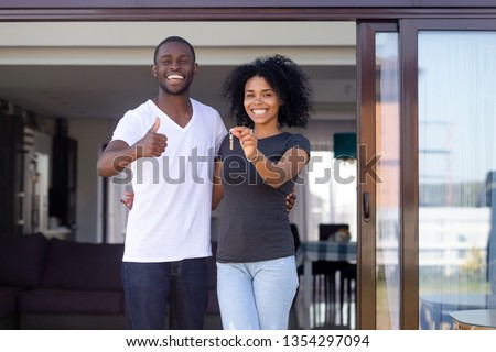 Overjoyed african married couple standing on summer terrace porch near new modern house. Happy wife hold keys embracing beloved husband showing thumbs up sign. Property ownership, loan tenancy concept ストックフォト ©