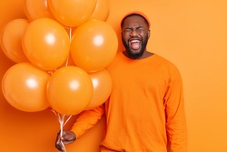 Overjoyed bearded man laughs positively has fun during birthday party holds bunch of balloons wears hat and sweater isolated over vivid orange background. People holiday celebration concept.