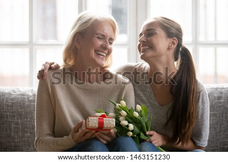 Overjoyed beautiful middle aged mother sit with grown up daughter hold gift and flowers family laughing celebrating life event, birthday or spring holiday 8-march International Women Day feeling happy