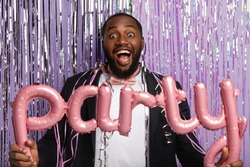 Overjoyed black gentleman with bristle, dressed in formal suit, entertains guests, holds party accessories, poses in photozone against purple background with sparkled long tinsel. Holiday celebration