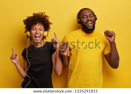 Overjoyed black woman and man gesture from happy emotions, have fun together, listen songs downloaded from networks, feels excited to win online contest, have recreation time after lectures. #1335291815