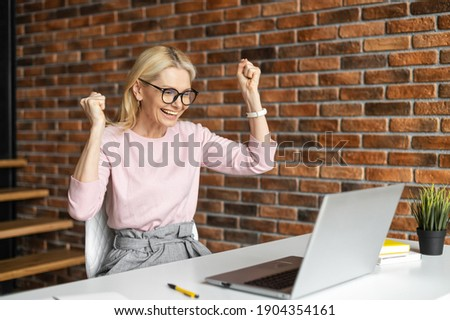 Overjoyed businesswoman looks at laptop screen and raising her arms up as victory sign, a happy lady laughs with triumph, winning in game, having received great news of a good deal Сток-фото ©