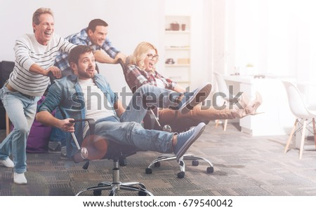 Shutterstock Overjoyed colleagues riding in office chairs